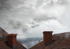 Dachy z kominu i miasta chmurami Fotografia Royalty Free
