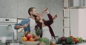 Dacing alegre mesmo dos pares engraçado na cozinha com alguns acessórios da cozinha, atmosfera muito engraçada em uma cozinha mod video estoque