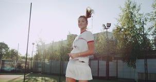 Dacing sportivkvinna på tennisbanan, innan att starta leken, solig dag 4K stock video