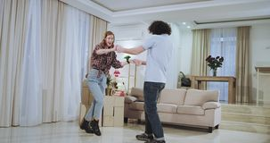 Dacing very attractive couple in a new house they enjoy the time together feeling happy and very excited after a hard. Moving day stock footage