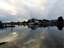 Dacked通过平衡云彩和天空的反射boatssurrounded在水中 免版税库存图片