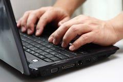 Dactilografia em um computador portátil Fotografia de Stock Royalty Free