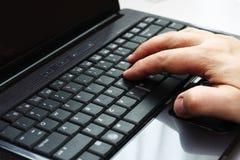 Dactilografia em um computador portátil foto de stock