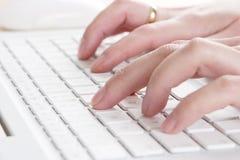 Dactilografia em um portátil Fotografia de Stock