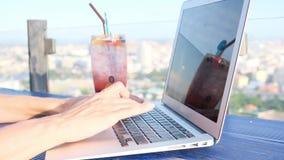 Dactylographie femelle sur un ordinateur portable dans un café sur le toit de tour avec une belle vue panoramique de la ville, fi clips vidéos