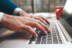 Dactylographie ouverte de mains d'ordinateur portable et de mâle Images libres de droits