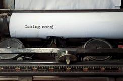 Dactylographie sur une vieille machine à écrire venant bientôt Photographie stock