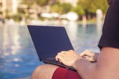 Dactylographie travaillante d'homme d'affaires sur un ordinateur portable ses vacances Photographie stock libre de droits