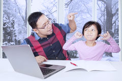 Dad advising his daughter to study. Portrait of young father advising his daughter for doing her school assignment at home Royalty Free Stock Photography