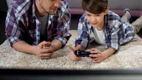 Dad advising son how to operate video game joystick, support and care, leisure. Stock photo royalty free stock photography