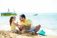 Free Dad And Little Girl Play, Sculpt Sand Castles On The Beach And Fool Around On The Sea Coast. Family Vacation At Sea With Stock Images - 176537714