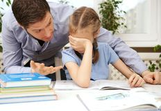 Dad is angry. Dad is angry because his daughter don`t want to do her homework stock photos