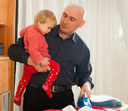 Dad with baby in  arms for ironing Stock Images