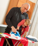 Dad with baby in arms for ironing Royalty Free Stock Image