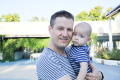 Dad with a baby boy in his arms, close-up, summer. Royalty Free Stock Photography