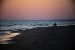 Father and son sit near the sea at sunset royalty free stock photography