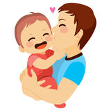 Dad And Baby. Cute little baby being kissed by his young dad Royalty Free Stock Image