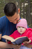 Dad and Baby Daughter Reading Bible Stock Images
