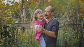 Dad baby in her arms. Dad and daughter having fun whirling and dancing in the autumn park. slow-motion stock footage