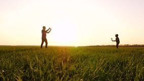 Dad and baby play outdoors in the sunset background, launching each other a toy plane.
