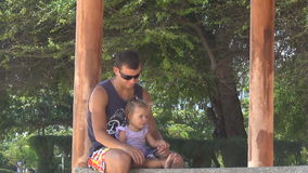 Dad and baby playing in the gazebo by the sea. girl stomping feet. Dad keeps daughter's legs. They are laughing. stock video
