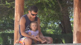 Dad and baby playing in the gazebo by the sea.girl stomping feet. Dad keeps daughter's legs. They are laughing. Dad and baby playing in the gazebo by the sea stock footage