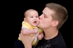 Dad and baby son - Kiss. A sweet, precious baby of two months of age is being kissed on the cheek by his father. Black background Stock Photo