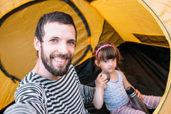 Dad with baby in tent taking selfie, family trip Stock Photo