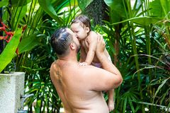 Dad and baby under a tropical shower. dad and baby playing on the beach under shower water splashes royalty free stock image