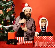 Dad with beard and kid cuddle with dogs. Near Christmas tree. Man and boy in Santa hats play with puppies. Pet for Christmas concept. Father and son with happy royalty free stock photography