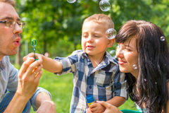 Dad blow soap bubbles and teaches his son. Mom sits by, looks an Stock Images