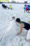 Dad builds a mermaid sand castle around his daughter. Young girl is sculpted into a mermaid in the sand by her father royalty free stock images