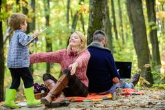 Dad is always busy. Family day concept. Family with kid boy relaxing in forest. Mother and little play together while. Father working with laptop. Conflicts of royalty free stock photo