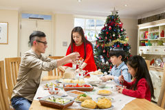 Dad can you pass me the vegetables please!. Chinese family enjoying their christmas dinner. They are eating traditional Chinese food. The parents are serving it Stock Images