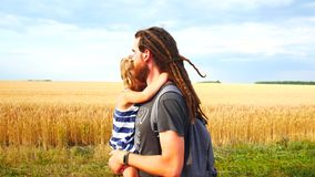 Dad carries daughter in his arms. Walk in the countryside.