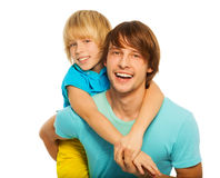 Dad carry son on his back. Blond 8 years old son hugging his dad, isolated on white Royalty Free Stock Photography