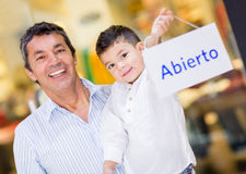Dad and son holding an open sign Stock Photography