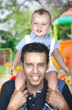 Dad carrying his son on shoulder. Son on his father's shoulders having fun Royalty Free Stock Photo