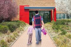 Dad and child arrive at school. Rear view of father and his daughter walking on the path while carrying backpack and arrive at school Royalty Free Stock Photo