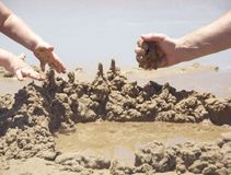 Dad and child is building the casstle of sand Royalty Free Stock Images