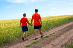 Dad and child go through a dirt road along a dirt road, along a beautiful field against a beautiful, blue sky. On a warm summer day Stock Photos
