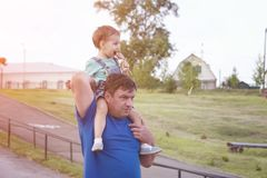 Dad with a child on his shoulders during a walk. Dad with a child on his shoulders during a summer walk through the city park in the open air royalty free stock photo