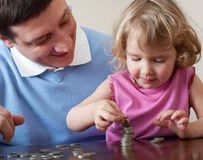 Dad and child puts coins Stock Images