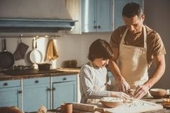 Father teaching his son knead into dough. Dad and child standing in cooking room and making batter together. Copy space in left side Royalty Free Stock Photography