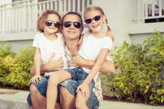 Dad and children playing near a house at the day time. Stock Photos