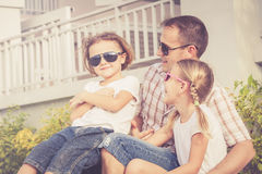 Dad and children playing near a house at the day time. Royalty Free Stock Images