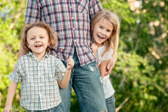 Dad and children playing near a house at the day time. Stock Photo
