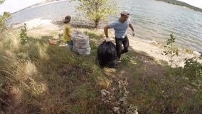 Dad and children scavenge, slow motion. Children cleaning scavenge. Children collect garbage bag in the woods stock footage