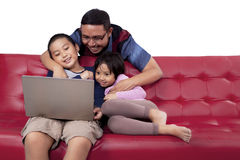 Dad and children use laptop on sofa Royalty Free Stock Image