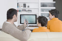 Dad and children watching tv. Rear view of a father with twin sons watching tv at home, using the control remote Royalty Free Stock Image